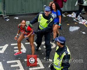 Atmosphere , View - A woman winding a laughing police officer during the Notting Hill Carnival 2015. at Notting Hill,...