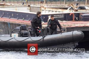 Dominic Cooper - Dominic Cooper Filming Stratton on a barge on the river Thames with fire arms.  At one...