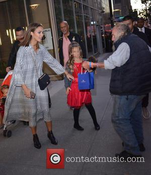 Jessica Alba , Honor Marie Warren - A bystander attemps to hand Jessica Alba a blue bag while out with...