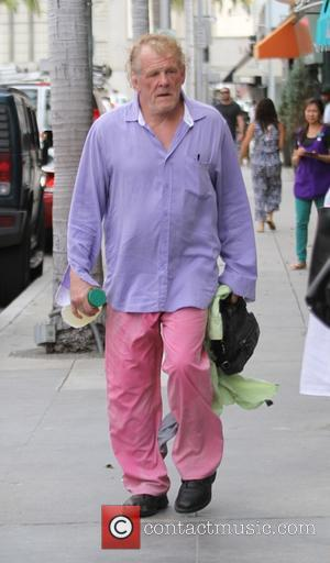 Nick Nolte - Nick Nolte in purple shirt and pink baggy trousers, grabs lunch at a deli in Beverly Hills...