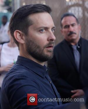 Tobey Maguire - Tobey Maguire signs autographs for fans as he leaves the 'Jimmy Kimmel Live!' studios after appearing on...