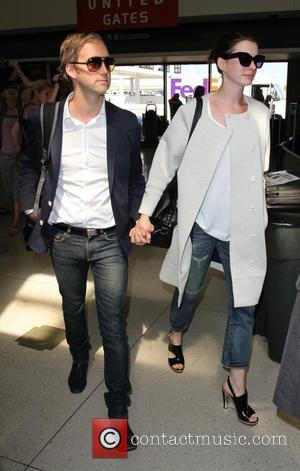 Anne Hathaway , Adam Shulman - Anne Hathaway arrives at Los Angeles International Airport with her husband Adam Shulman to...