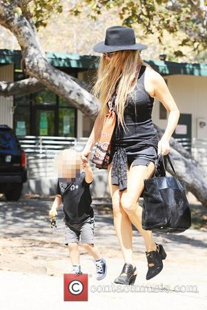 Fergie Duhamel , Axl Jack Duhamel - Fergie in a black skimpy outfit and black hat, takes her son Axl...