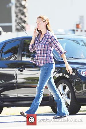 Jennifer Garner - Jennifer Garner wearing checked shirt and jeans talks on her cell phone as she runs errands in...