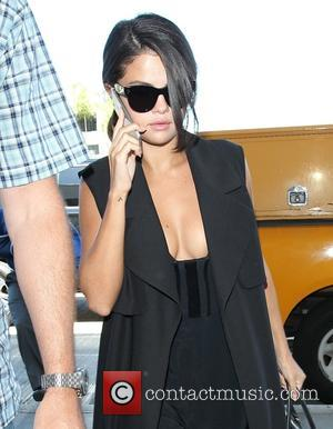 Selena Gomez - Selena Gomez reveals cleavage as she arrives at Los Angeles International Airport to catch a flight -...