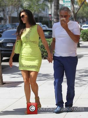Andrea Bocelli , Veronica Berti - Andrea Bocelli talks on his iPhone while holding hands with his wife dressed in...