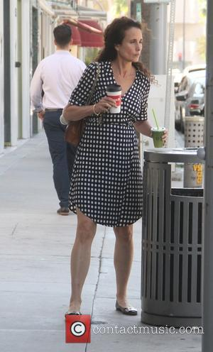 Andie MacDowell - Andie MacDowell wearing a polka dot dress with flat shoes, carries a coffee in one hand and...