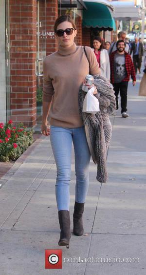 Rhea Durham - Rhea Durham wearing skinny jeans and boots, carries her lunch in a paper bag while out and...