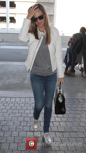 Hilary Swank - Hilary Swank departs on a flight from Los Angeles International Airport (LAX) wearing a white leather jacket...