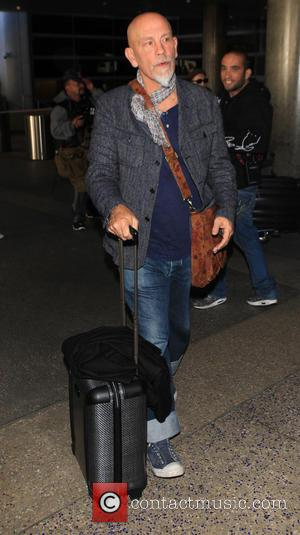 John Malkovich - John Malkovich wearing a grey jacket and scarf, with ill fitting oversize turn ups on his jeans,...