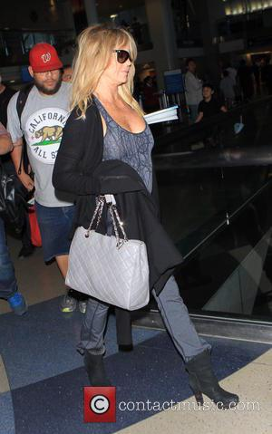 Goldie Hawn - Kate Hudson wearing an Aerosmith t-shirt and flared jeans arrives on a flight to Los Angeles International...