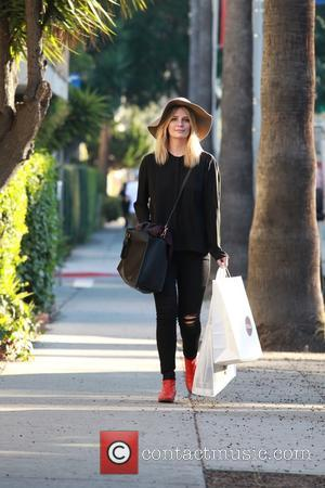 Mischa Barton - Mischa Barton wearing all black with bright red boots, carries a Mou shopping bag when seen out...