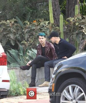 Joe Jonas - Joe Jonas with his dyed hair and wearing a mauve leather jacket, out with friends in Melrose...