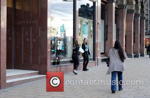 View - Two young women, braving the cold wind, tried to entice shoppers into Jenners Department Store without much luck....