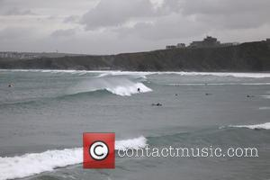 Atmosphere - Daredevil surfers ride the huge storm waves off the north coast of Cornwall, England. - Cornwall, United Kingdom...