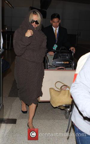 Pamela Anderson - Pamela Anderson arrives on a flight to Los Angeles International Airport (LAX) wrapped in a brown crinckle...