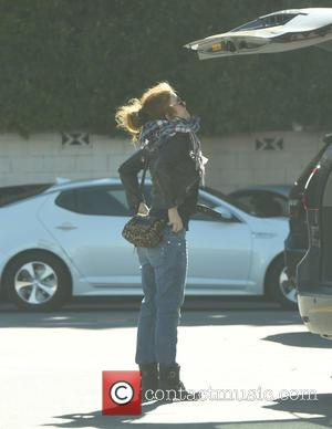 Isla Fisher - Isla Fisher has to stand on her tip toes to shut her trunk while shopping for groceries...
