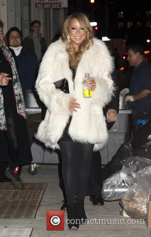 Mariah Carey - Mariah Carey sports a white fur coat and enjoys a Vitamin Water on her way to the...