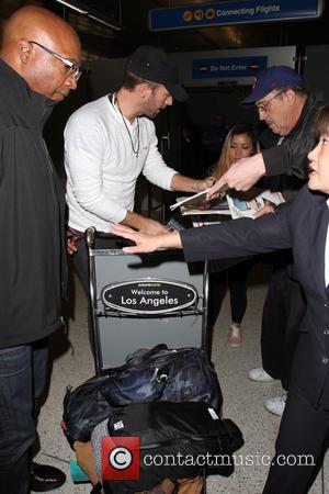 Chris Martin - Coldplay frontman, Chris Martin arrives on a flight to Los Angeles International Airport (LAX) wearing a 'Love'...