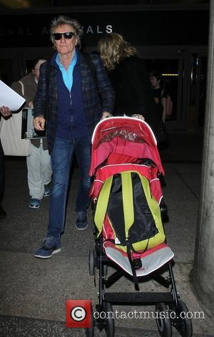 Rod Stewart , Penny Lancaster - Rod Stewart and Penny Lancaster mobbed by fans as they arrive on a flight...
