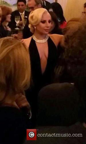 Lady Gaga - Lady Gaga showing her cleavage wearing an ultra low cut black dress complimented with a diamond crusted...