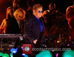 Elton John - Elton John performing live in concert in front of the Sleeping Beauty castle at Disneyland. Elton John...