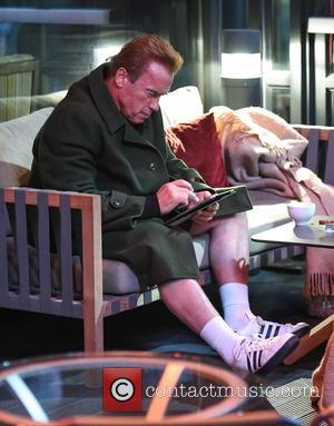 Arnold Schwarzenegger - Arnold Schwarzeneggar sits and smokes a cigar in his shorts in Birmingham at his hotel. The Hollywood...
