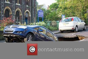 Atmosphere - A car dissapears down a sinkhole in Charlton this morning. - Charlton, United Kingdom - Thursday 12th May...