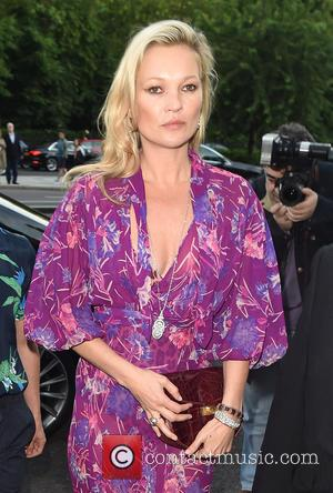 Kate Moss wears a purple jumpsuit, flashing her bra as she stepped out of her car before entering the Victoria...