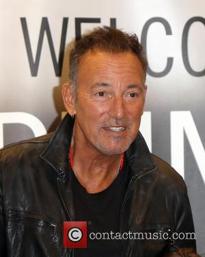 Bruce Springsteen stopping for photos with fans at an event for his book 'Born To Run' held at a branch...