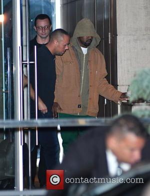 Kanye West pulls his hood over his head as he leaves Kim Kardashian's apartment in Manhattan, New York, United States...