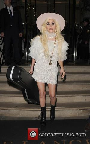 Lady Gaga leaving her hotel holding her guitar. Gaga was given a large painting on canvas by fan as she...