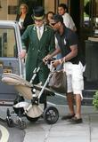 Patrick Kluivert folding his pushchair into a taxi cab at the Dorchester