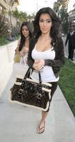Kim Kardashian and sister Kourtney Kardashian (behind) arrive by limousine to her West Hollywood Apartment after a shopping spree