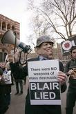 A protester wears a mask of Tony Blair...