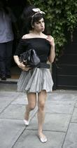 Amy Winehouse leaves home dressed in a smart...