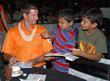Michael Kasprowicz of Mumbai Champs gives an autograph to children