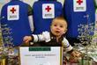 A child helps open mail during the Holiday Mail for Heroes Packing Event at the American Red Cross Headquarters