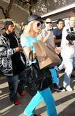 Paris Hilton Exits Portofino tanning salon surrounded by...