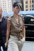 Rihanna, wearing a brown snakeskin top and strappy...