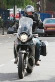 Adrian Chiles Arrives by motorcycle for a photo...
