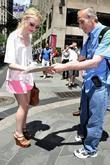Dakota Fanning signs an autograph while out and...