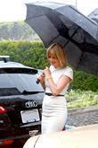 Heidi Klum and holding a large black umbrella