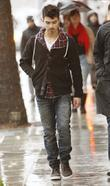 Joe Jonas is seen walking in the rain...