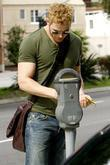 Kellan Lutz paying a parking meter while out...