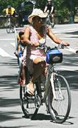 Malaak Compton-Rock riding a bicycle with her daughter Zahra Savannah in the child seat in Manhattan
