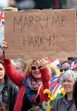 Woman holding a sign that says 'Marry Me...