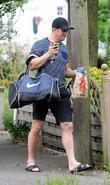 Alex Reid returns home after training holding a...