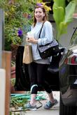 Alyson Hannigan dressed in gym clothes and carrying...