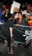Emily Blunt poses for photographs with fans outside...